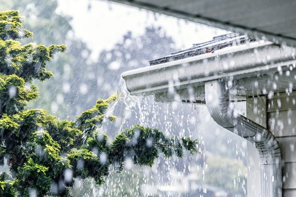 Photo of an overflowing roof gutter in the rain